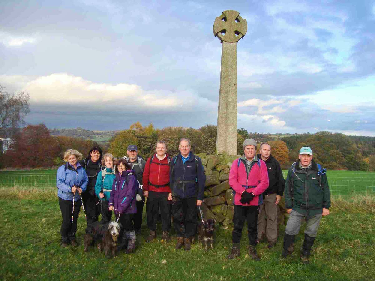 A group of One Step Walkers standing a stone cross