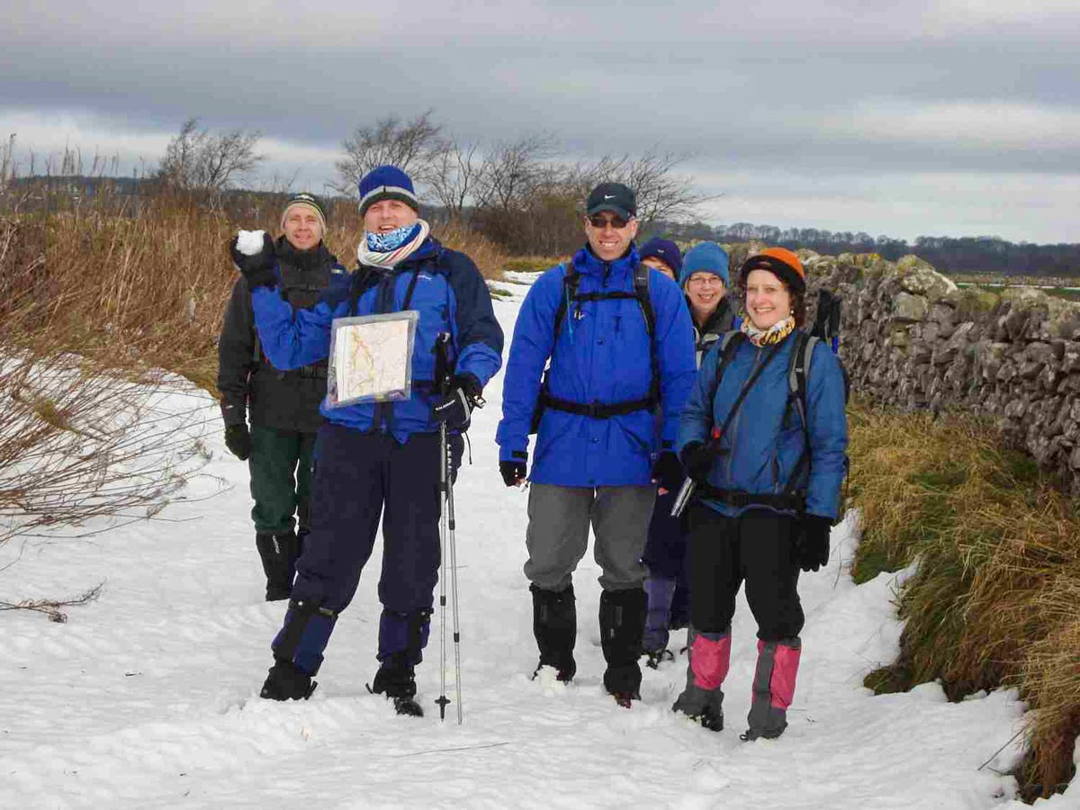 A small group of walkers trekking in the snow in Derbyshire