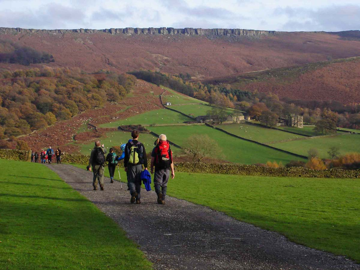 A group of walkers at Stanage Edge in the Peak District National Park in Derbyshire