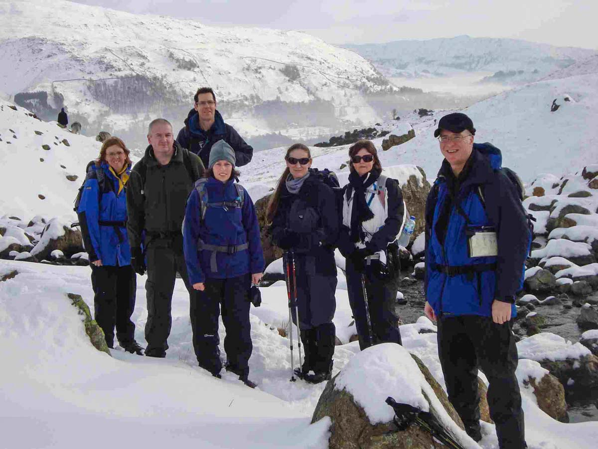 A group of One Step Walkers in the Scottish Highlands with snow covered mountains